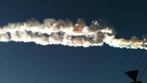 Ein Meteorit hinterlässt am Himmel über der Stadt eine weiße Spur