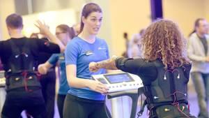 EMS-Training: Angeleitet von einer Trainerin testet eine junge Frau EMS-Training