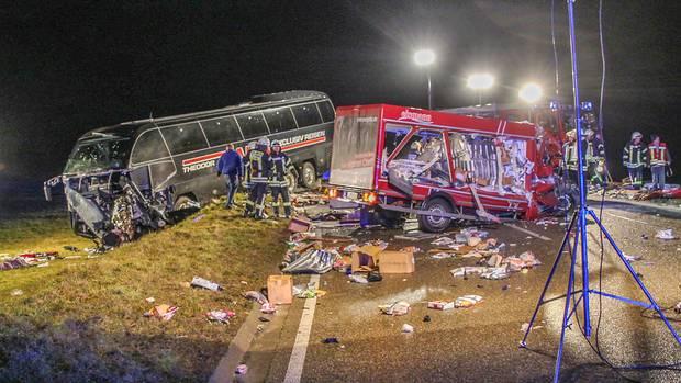 Feuerwehrleute stehen neben einem zerstörten Kleinlaster und einem Reisebus