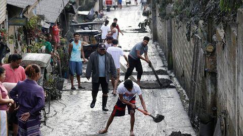 Philippinen, Cavite: Anwohner reinigen eine Straße von Asche