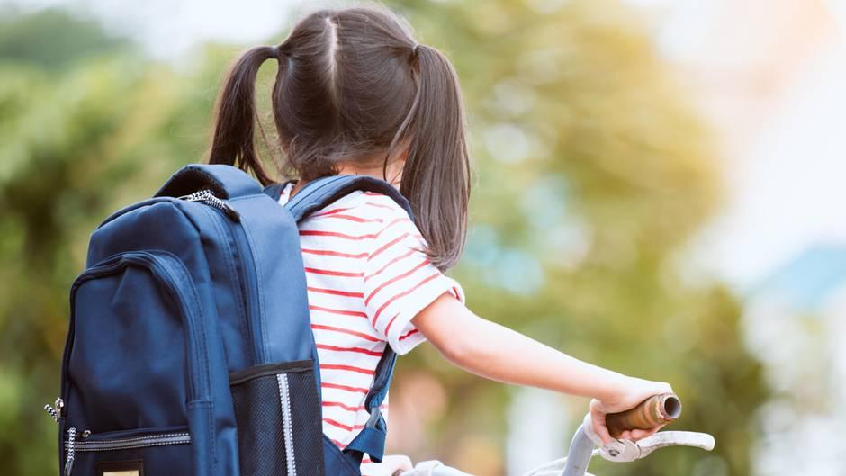 Ein Mädchen mit Zöfen und Rucksack sitzt auf einem Fahrrad