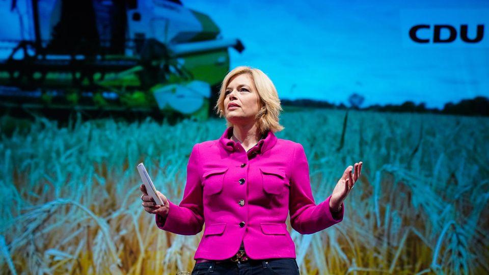 Julia Klöckner auf dem Landesparteitag der CDU. Hinter ihr istein Feld mit einem landwirtschaftlichen Fahrzeug zu sehen.