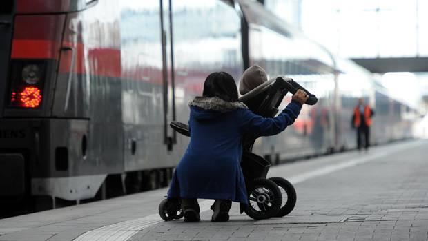 Frau mit Kinderwagen an einem Zug
