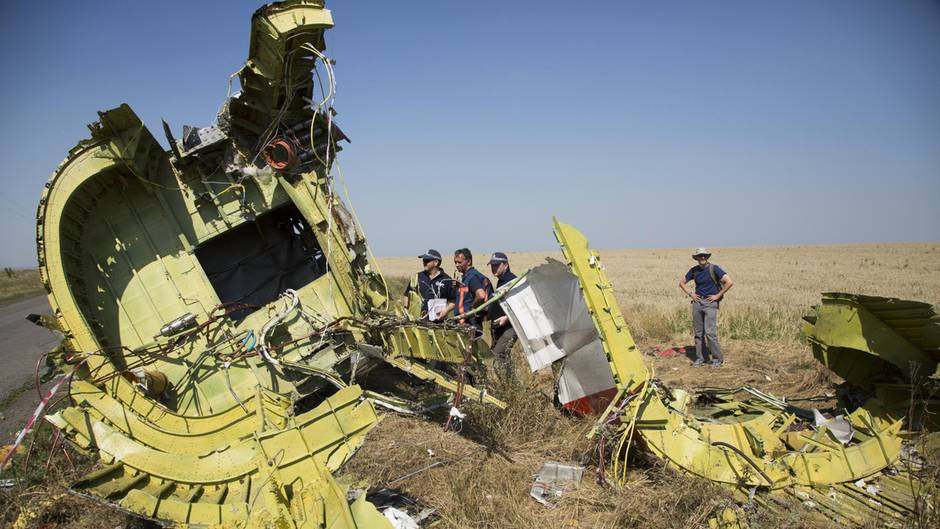 Spezialisten für Flugunfalluntersuchung aus den Niederlanden stehen Anfang August 2014 neben Überresten des Fluges MH17 auf einem Feld bei dem Dorf Hrabove in der östlichen Ukraine.