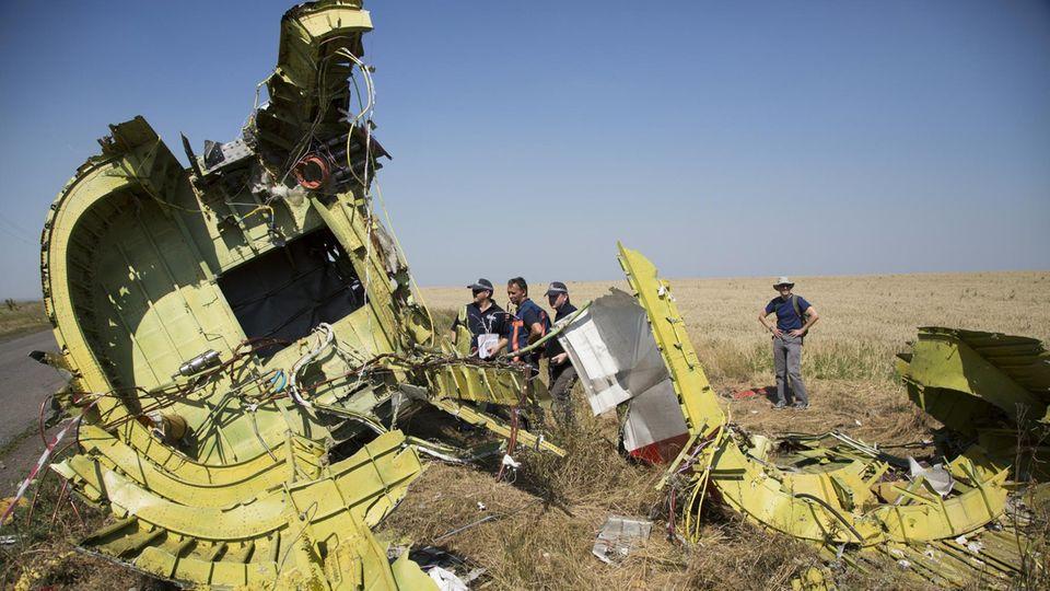 Spezialisten für Flugunfalluntersuchung aus den Niederlanden stehen Anfang August 2014neben Überresten des Fluges MH17 auf einem Feld bei dem DorfHrabove in der östlichen Ukraine.
