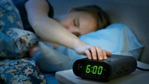 Frau betätigt einen Wecker