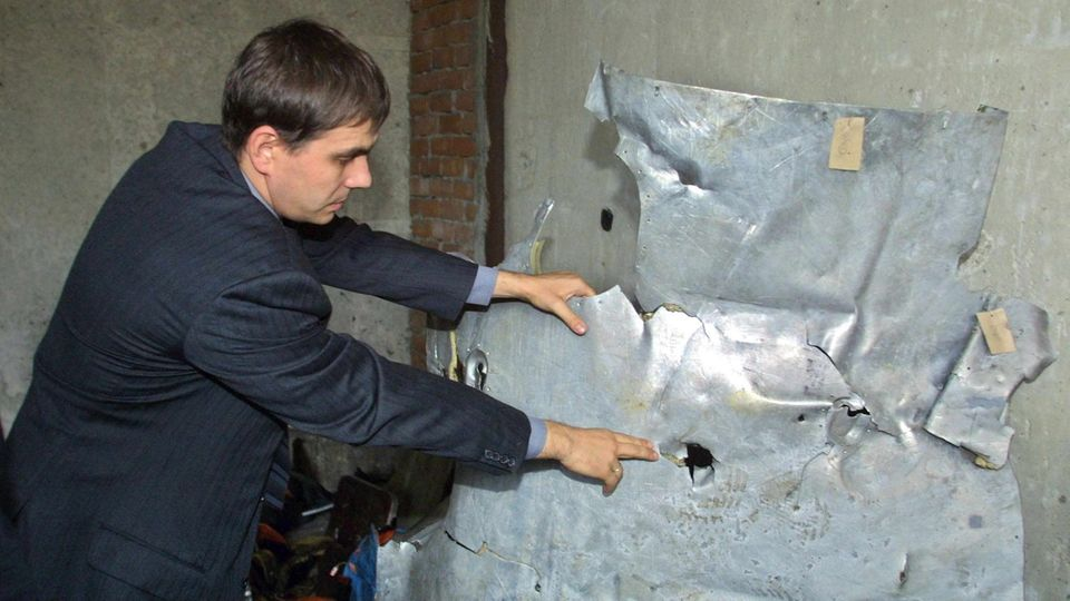 """Ein aus dem Schwarzen MeergeborgenesTrümmerteil der Tupolew:Der Direktor der Fluglinie Sibir, Wjatscheslaw Filew, zeigt """"durchschussartige Löcher""""auf einemAluminiumteilder abgestürzten Tupolew Tu-154."""