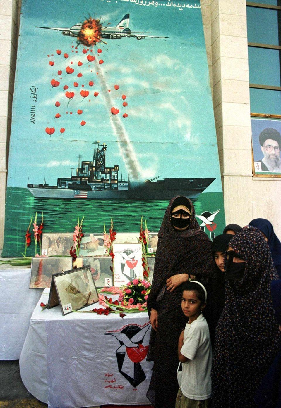 Angehörige von Opfern des Iran-Air-Fluges655stehen am zwölften Jahrestag des Abschusses vor einem Wandgemälde in Bandar Abbas