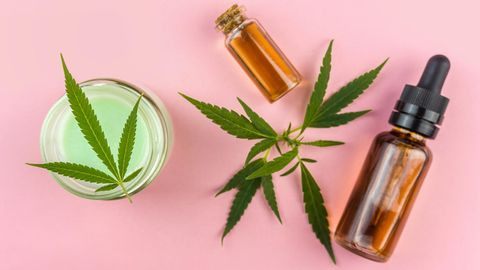 CBD: Eine Hanfpflanze und ein Fläschchen mit Öl liegen auf einem Tiscj