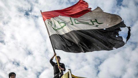 Ein Demonstrant schwenkt die irakische Flagge
