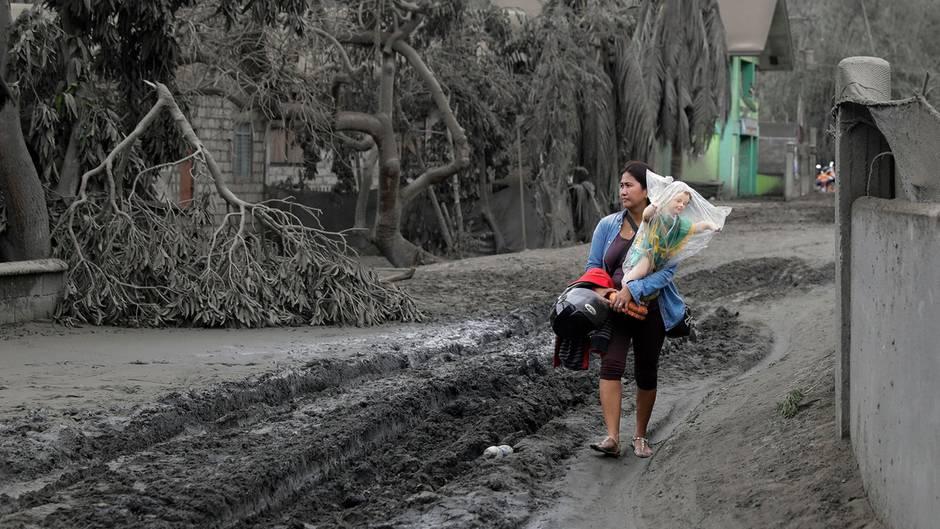Der Vulkan Taal auf den Philippinen hat die Landschaft unter einen Grauschleier gelegt, die Menschen flüchten.Eine Frau trägtin dem Ort Boso-Boso eine Statue des Jesuskindes in Sicherheit.