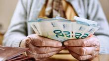 Hand einer Seniorin mit Euroscheinen