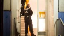 Einsatzkräfte der Polizei stehen im Hausflur eines Mehrfamilienhauses in Marzahn-Hellersdorf