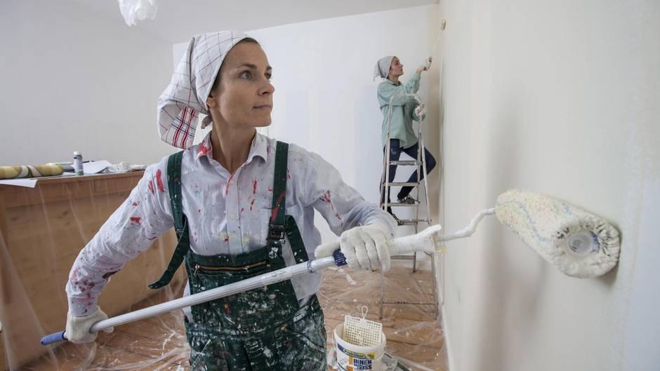 Wände streichen: zwei Frauen renovieren mit Farbroller und Pinsel ein Zimmer