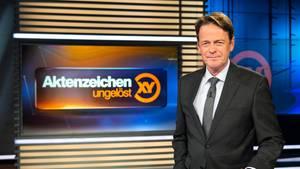 """Moderator Rudi Cerne mit dem Logo der Sendung Aktenzeichen XY"""""""