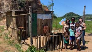 Kinder in der Armengegend von Jororó zeigen den helfenden Frauen (hintere Reihe) ihre Hütte