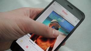 Ein Smartphone-Display zeigt das Tinder-Profilfoto eines Mannes mit nacktem Oberkörper am Strand