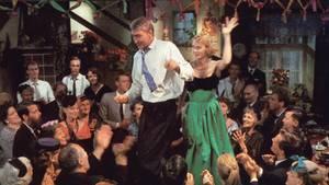 Pärchen tanzt auf einem Tisch, umgeben von Menschen