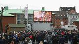 Live-Übertragung derTrauerfeierim Michel auf einer Leinwand vor der Kirche