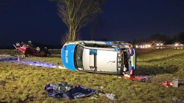 Ein Pkw und ein Polizeiauto liegen nach einem Unfall auf einer Wiese neben der A92