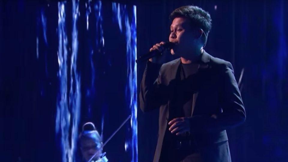 Marcelito Pomoy steht auf der Bühne und singt ins Mikrofon