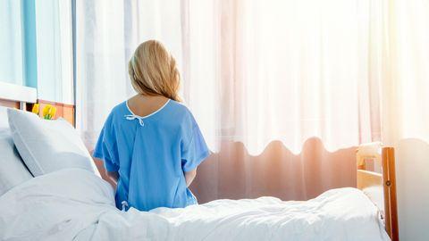 Eine blonde Frau im Krankenhaus, von hinten fotografiert