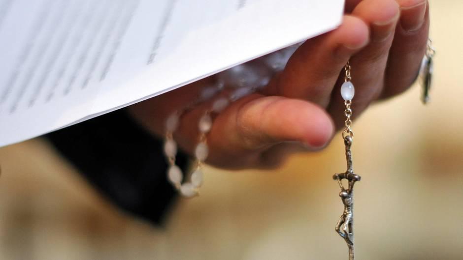 Ein Priester hält einen Rosenkranz und Dokumente in der Hand