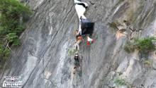 Basejumper hängt mit Fallschirm an einer Klippe fest