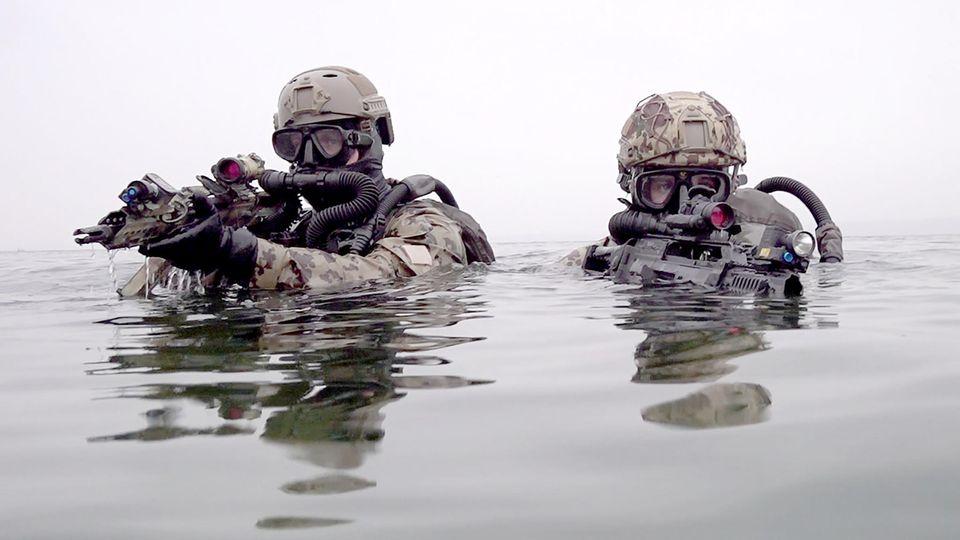 Kampfschwimmer gehen mit G36 Sturmgewehren bei einer Übung aus der Ostsee an Land