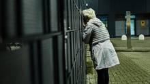 Verzweifelt versucht Ludmila Frizler, einen Blick durch den Zaun auf ihre Tochter und die Enkel zu erhaschen