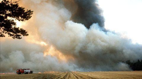 Ein Löschfahrzeug steht auf einem Stoppelfeld vor einem brennenden Acker