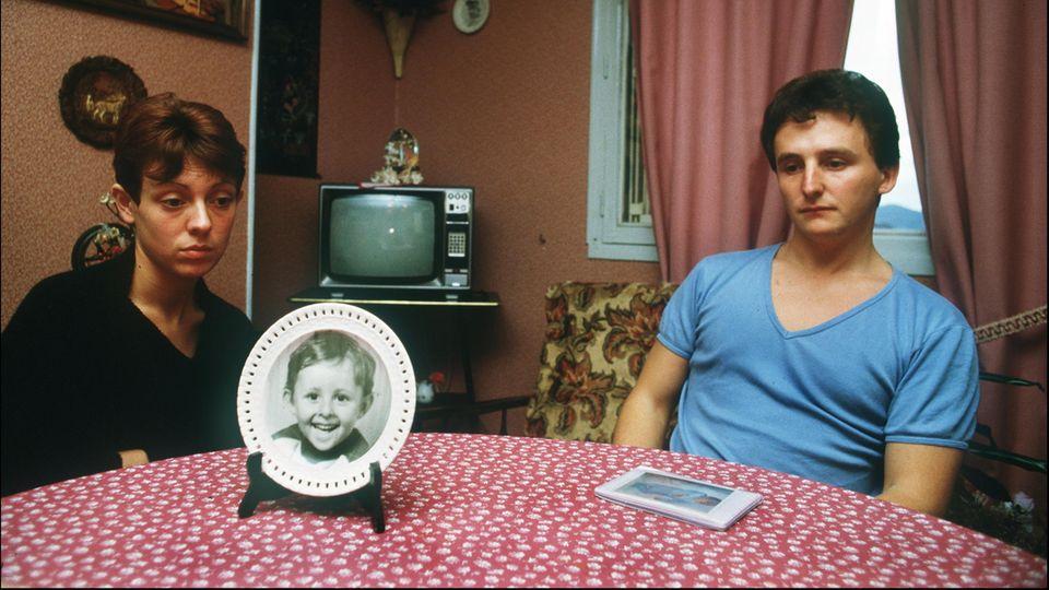 Christine und Jean-Marie Villemin, die Eltern des ermordeten Grégory, sitzen hinter einem Bild ihres kleinen Sohnes