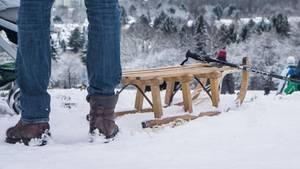 Neben einem Holzschlitten sind die Beine eines Mannes zu sehen. Im Hintergrund die Skyline von Frankfurt am Main