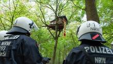 Zwei Polizisten in dunkelblauer Schutzkleidung und weißen Helmen stehen in einem Wald. In einem der Bäume ist ein Baumhaus
