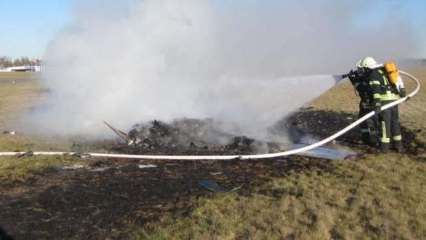 Zwei Feuerwehrleute löschen auf einer verkohlten Wiese die Trümmer eines abgestürzten Kleinflugzeugs