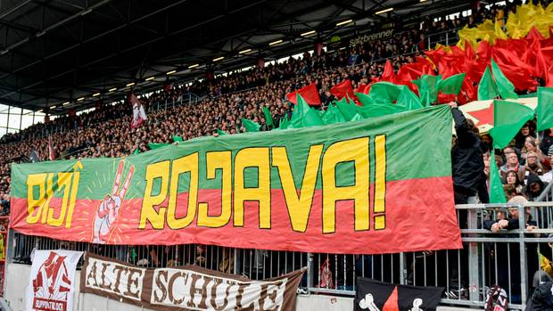 """St. Pauli-Fans halten ein Banner mit dem Schriftzug """"Biji Rojava""""(""""Es lebe Rojava"""") in die Höhe"""