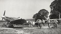 Piloten aus den USA laufen für die Kamera zu ihren Jägern vom Typ Supermarine Spitfire 5S.