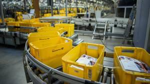 Gelbe Kisten zum Sortieren von Briefen laufen im Briefzentrum Kiel der Deutschen Post über ein Förderband