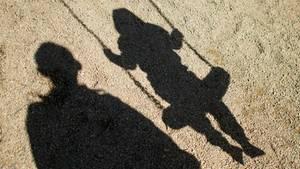 Schatten von einem Mann und einem Kind auf einer Schaukel