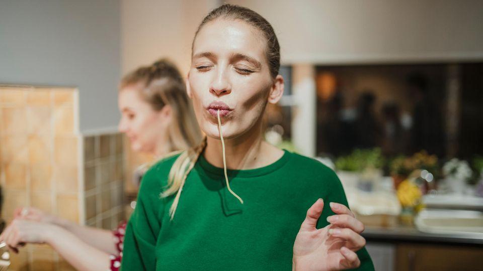 Eine Frau saugt eine Nudel ein