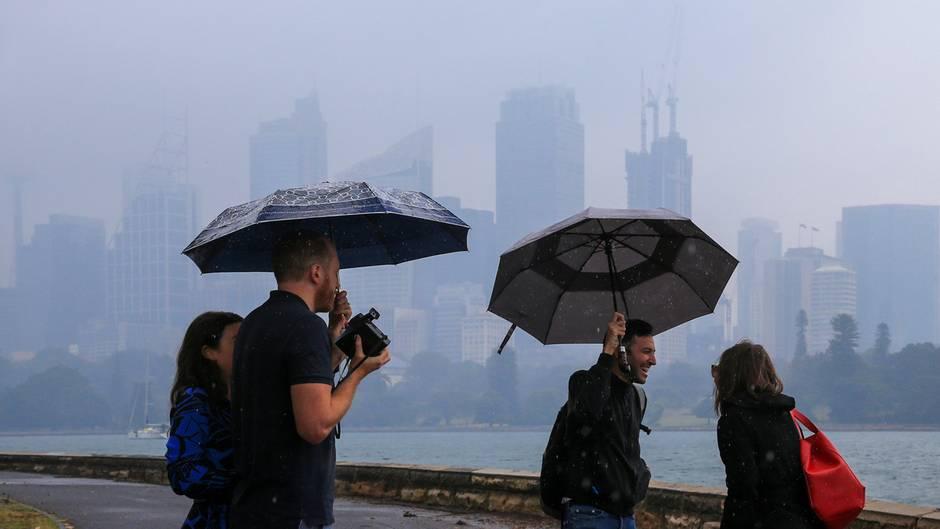 Skyline im Regen: Touristen im Hafen von Sydney. Dort hat es am Freitag erstmals seit vier Monaten ausgiebig geregnet.