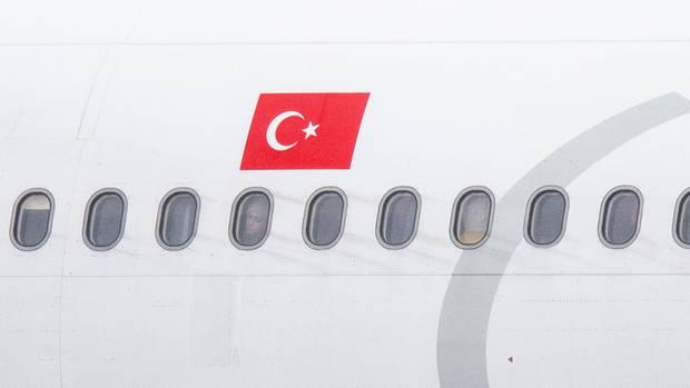 Über einer Fensterreihe prangt eine türkische Flagge auf dem weißeb Flugzeugrumpf