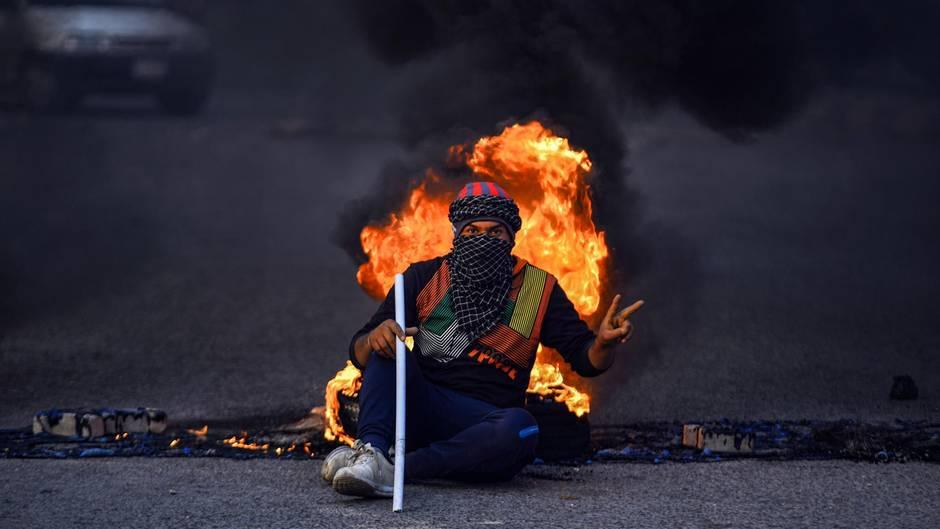 19. Januar: Ein bisschen Frieden  Najaf, Irak. Ein junger Demonstrant macht mit seiner linken Hand das Peace-Zeichen, während er in der zentralirakischen heiligen Schreinstadt Najaf vor einem Reifenfeuer an einer behelfsmäßigen Straßensperre sitzt.