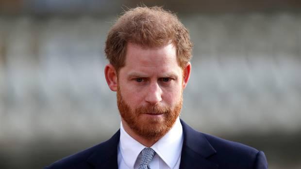Prinz Harry trägt eine grau gemusterte Krawatte zum dunkelblauen Anzug und schaut ernst