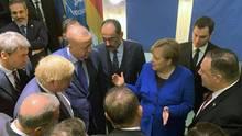 Bundeskanzlerin Angela Merkel steht mit anderen Regierungschefs in einem Kreis und gestikuliert