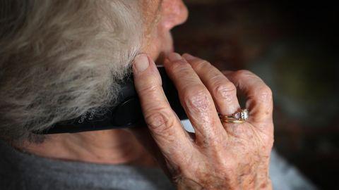 Eine ältere Frau telefoniert mit einem Festnetztelefon