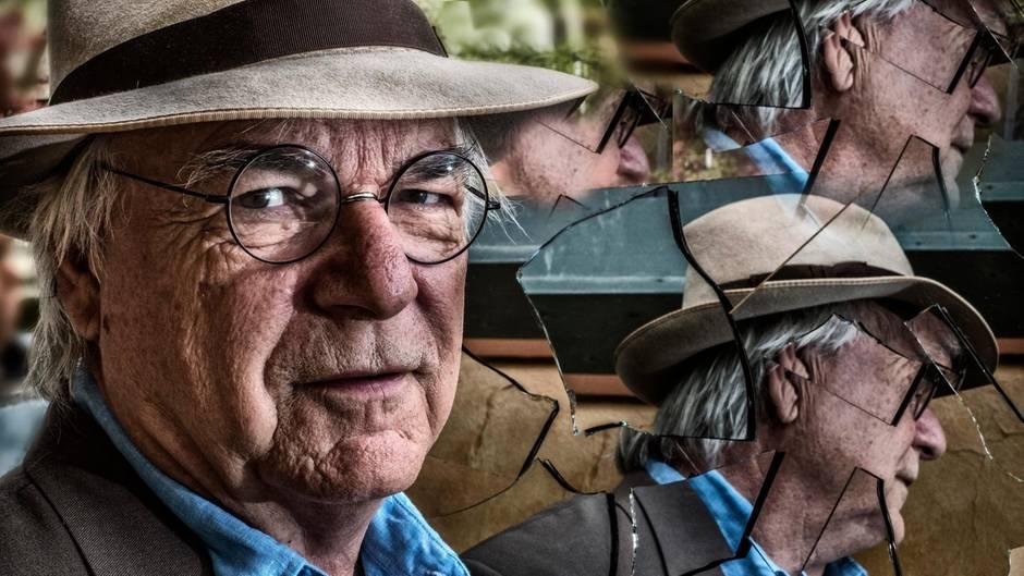 Ein Mann mit grauem Hut, Brille und weißen Haaren schaut mit nach rechts gedrehtem Kopf in die Kamera