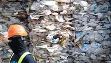 Ein Arbeiter vor einem Berg zerdrückter Plastikflaschen