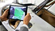 Ein Porsche-Ingenieur scannt mit einem Tablet ein Seitenteil eines Panamera auf Abweichungen - die Automobilindustrie ist bislang einer der Garanten für Deutschlands Status als Innovationsnation.