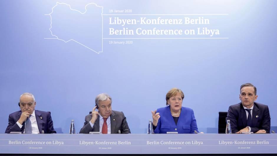 Auf einem Podium mit Bundesadler sitzen drei Männer in Anzügen und Bundeskanzlerin Angela Merkel. Sie trägt einen blauen Blazer